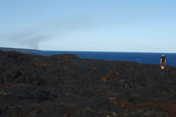 """Walking on lava"" - Martin walking on the hardened lava. In the background the smoke from the ocean entry (where lava runs into the ocean) is visible"
